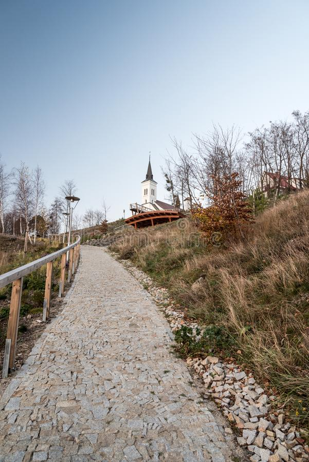 Borova hill in Malenovice village near Frydlant nad Ostravici city in Czech republic with church, lookout and footpath. During beautiful evening with clear sky stock photography