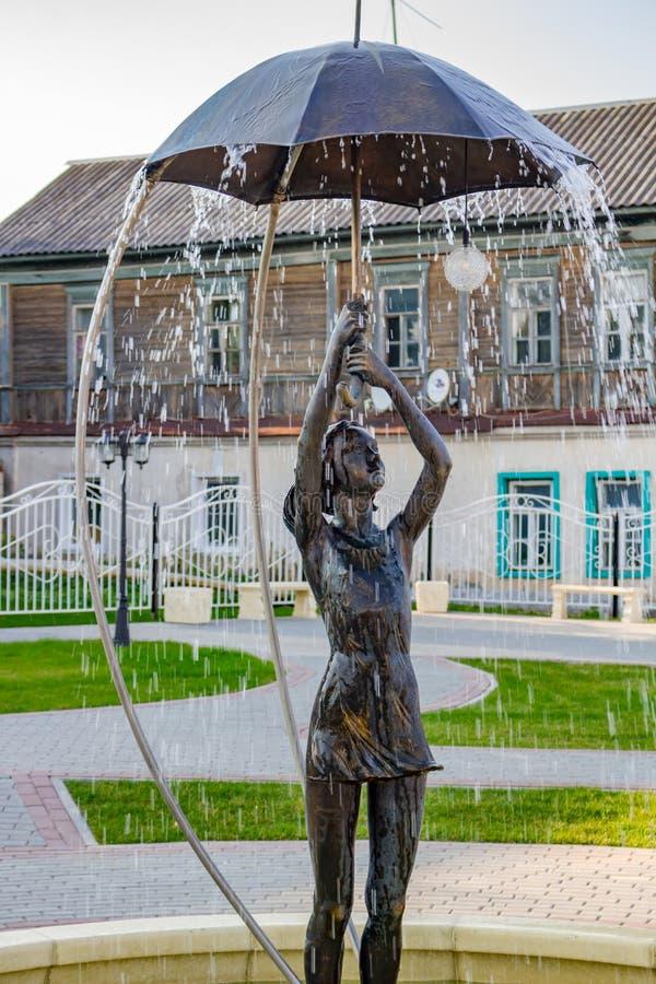 BOROVSK RYSSLAND - SEPTEMBER 2017: Springbrunn med en skulptur av en flicka med ett paraply royaltyfri bild
