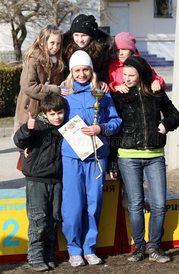 Borovska Nadiya, winner of the 20,000 meters race. Walk, takes a picture with a group of unidentified children after Ukrainian Championships on March 07, 2012 royalty free stock photography