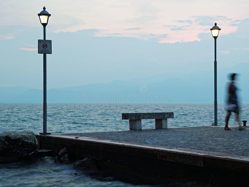 Borrão da mulher no banco pelo lago na hora azul imagens de stock royalty free