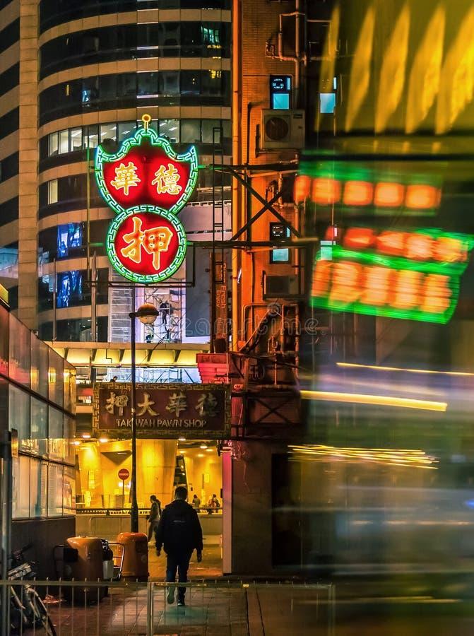 Borrão de movimento de ônibus e de silhueta moventes sob as luzes de néon na noite, Hong Kong imagens de stock