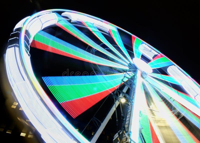 Borrão de movimento longo da exposição de uma roda de ferris de gerencio na noite iluminada em cores de néon brilhantes fotos de stock royalty free