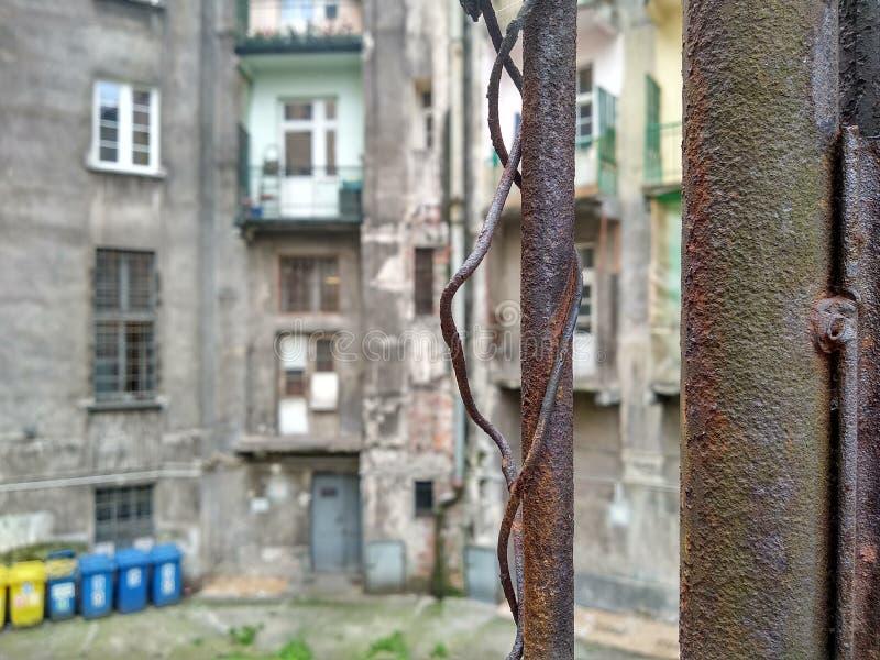 Borrão, olhar através da malha do ferro na casa cinzenta velha corrido atrás da cerca, olhe fora Limita??o da liberdade Casa fotografia de stock royalty free