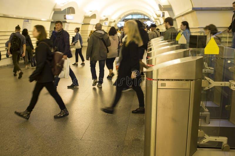 borrão Uma multidão de passagens dos povos com pressa através dos torniquetes eletrônicos na estação de metro em St Petersburg, R fotografia de stock