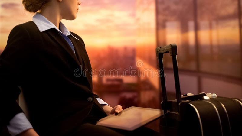 Borrad kvinna med minnestavlan som väntar i flygplatsvardagsrummet, affärstur, flygfördröjning arkivfoto