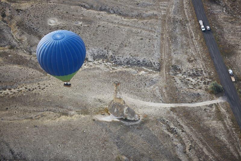 Borre o balão de ar quente que voa sobre a estrada com transporte de motor fotografia de stock