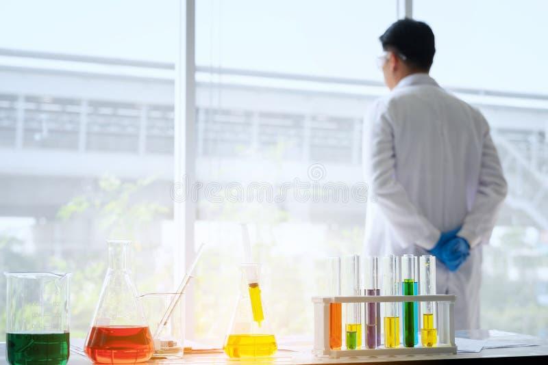 Borre o cientista masculino novo do foco que está no técnico de laboratório que faz me imagem de stock royalty free