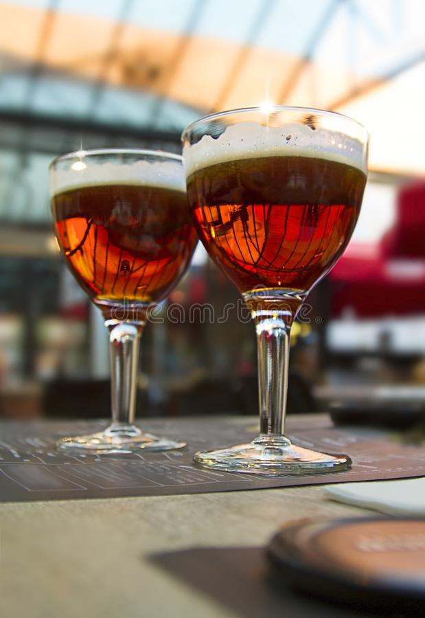 Borre o fundo claro com dois vidros de cerveja escura na tabela do café imagem de stock