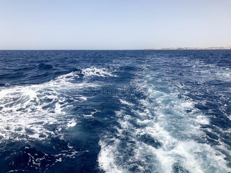 Borrelend iriserend blauw overzees zout water met golven, morserijen, bellen, schuim, sporen, plonsen na een snel drijvende kar,  royalty-vrije stock afbeeldingen