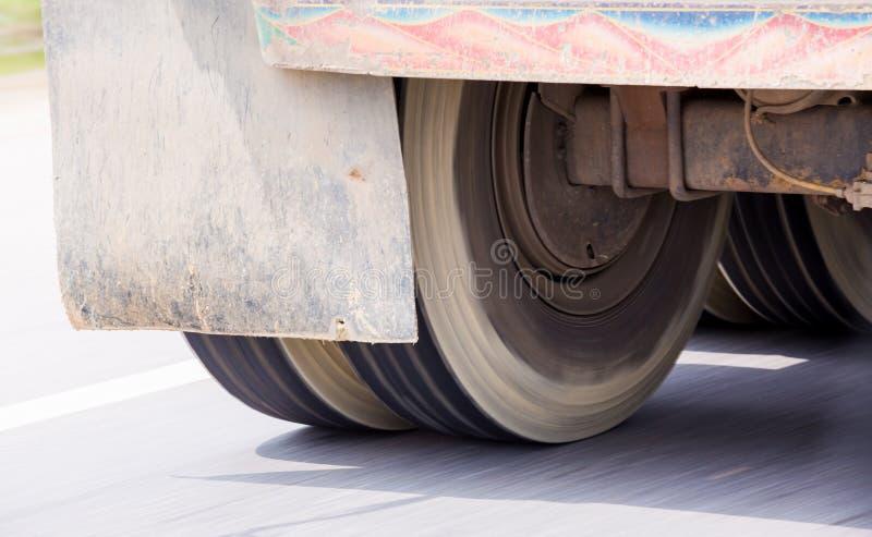 Borroso de las ruedas del camión que giran con el funcionamiento en la velocidad imagen de archivo libre de regalías