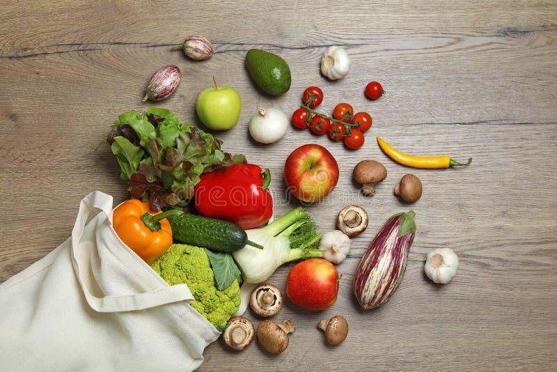 Borsa con gli ortaggi freschi e frutti su fondo di legno immagini stock libere da diritti