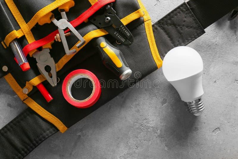 """Borsa con l'elettricista differente \ """"gli strumenti di s e la lampadina su fondo leggero fotografia stock"""