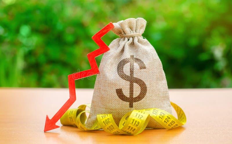 Borsa con la misura di nastro e dei soldi con la freccia per scolarsi Stipendi e benessere di caduta Profitti e liquidità bassi d fotografia stock libera da diritti