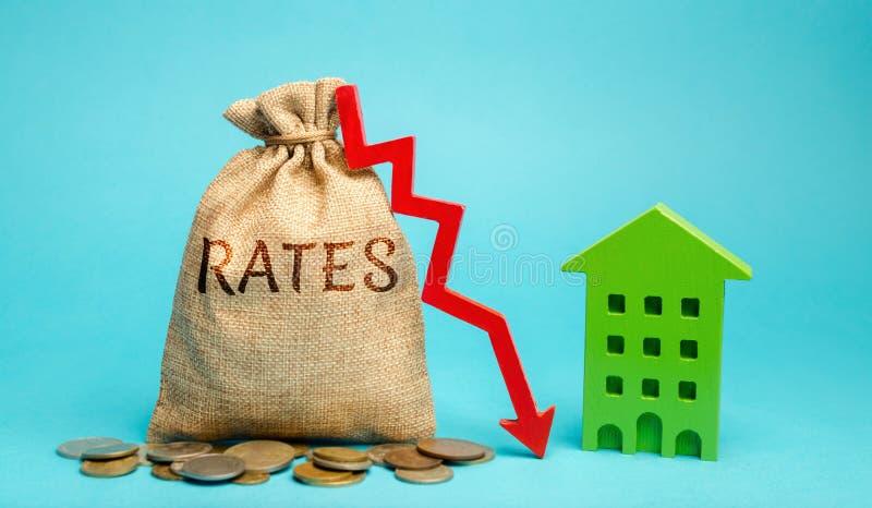Borsa dei soldi con i tassi di parola, giù la freccia e la casa di legno Il concetto di riduzione dei tassi di interesse sulle ip immagine stock