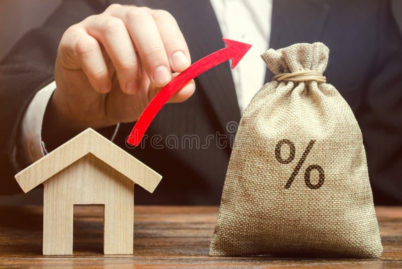 Borsa dei soldi con le percentuali, sulla freccia e sulla casa Il concetto dei tassi di interesse elevati sui mutui ipotecari o s fotografia stock