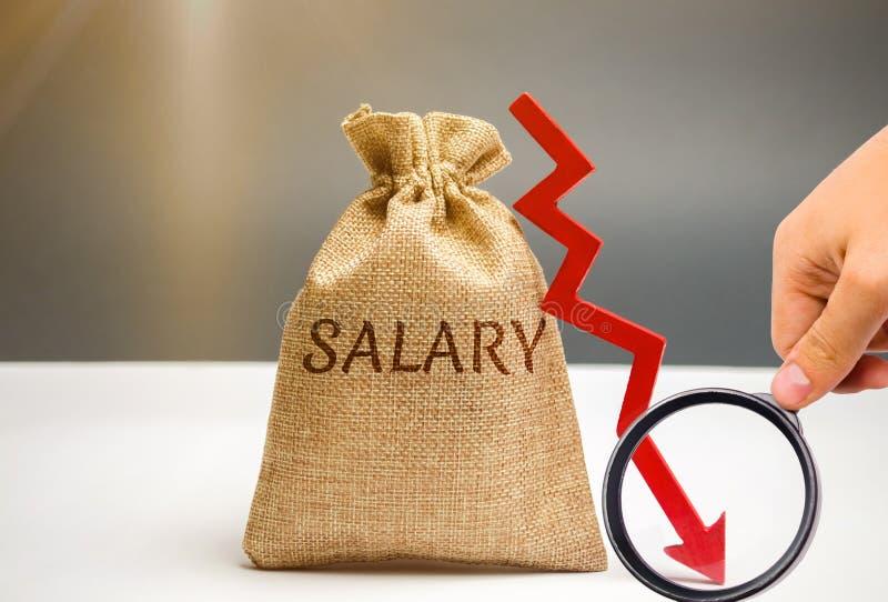 Borsa dei soldi con lo stipendio e la freccia di parola da scolarsi Abbassi lo stipendio, tassi salariali retrocessione, declino  fotografia stock