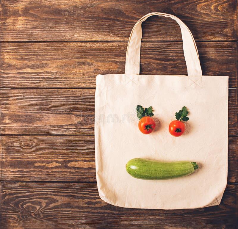 Borsa del cotone e fronte divertente fatti degli ortaggi freschi su un fondo di legno Il concetto di vegetarianismo sano di cibo immagini stock libere da diritti