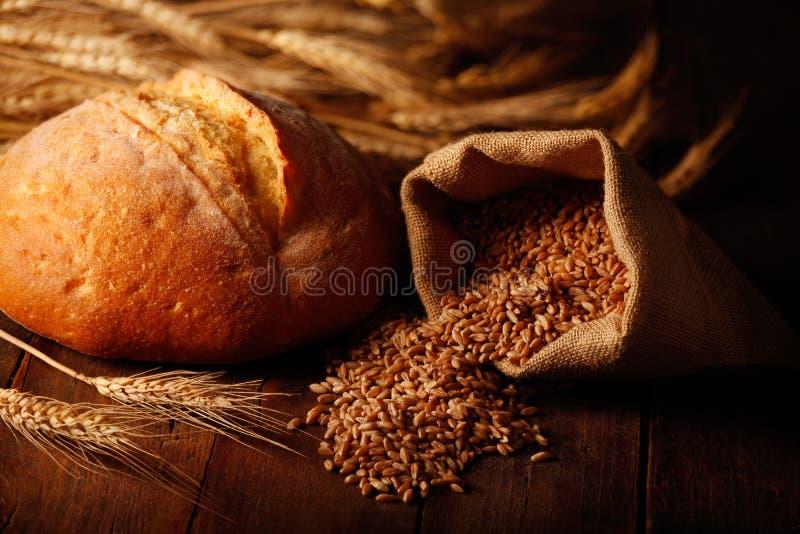 Borsa della iuta con i grani del grano, lo sphighe ed il pane dell'artigiano immagini stock libere da diritti