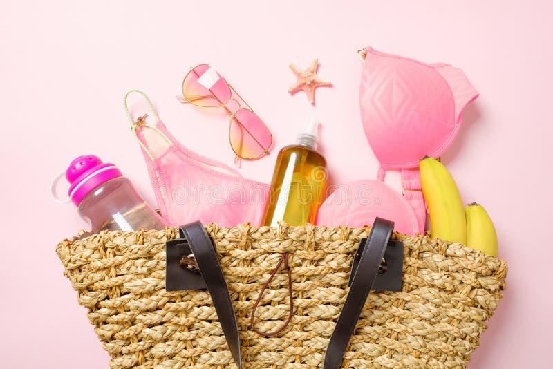 Borsa della spiaggia con l'abbigliamento e gli accessori di modo di estate su fondo rosa Roba femminile di fascino di vista super immagini stock