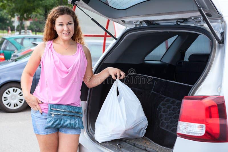 Borsa di caricamento del cliente della donna in tronco della sua automobile su parcheggio fotografie stock libere da diritti