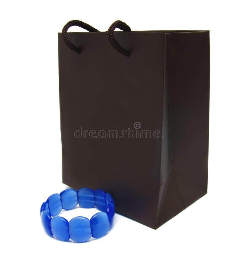 Borsa di carta e braccialetto marroni isolati su bianco fotografia stock