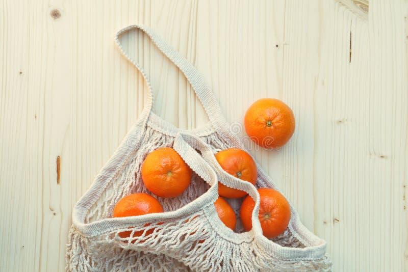 Borsa di corda ecologica bianca con i frutti, arance su fondo di legno, acquisto libero di plastica fotografia stock