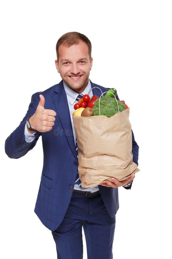 Borsa felice della tenuta dell'uomo d'affari con alimento sano, compratore della drogheria isolato fotografia stock