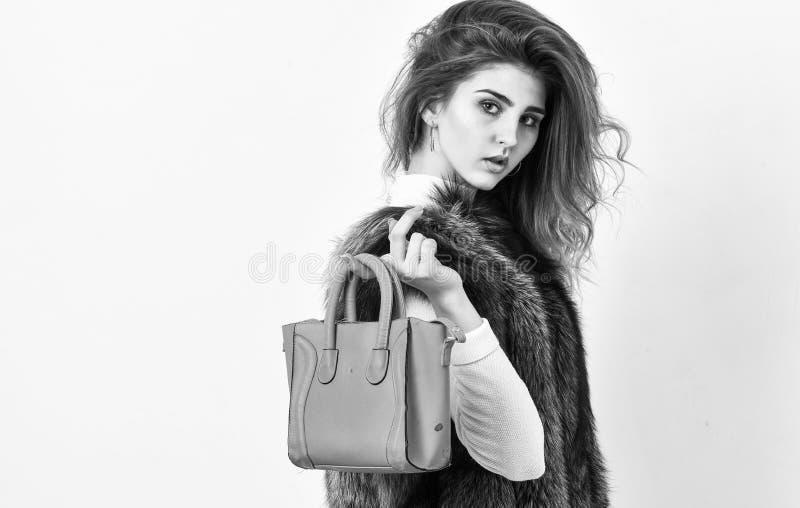 Borsa femminile della tenuta del modello di moda Donna in pelliccia con la borsa su fondo bianco Acconciatura alla moda di signor fotografie stock
