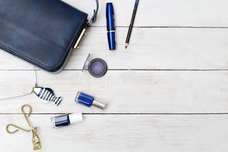 Borsa femminile di colore blu scuro e cosmetici su una parte posteriore di legno fotografia stock