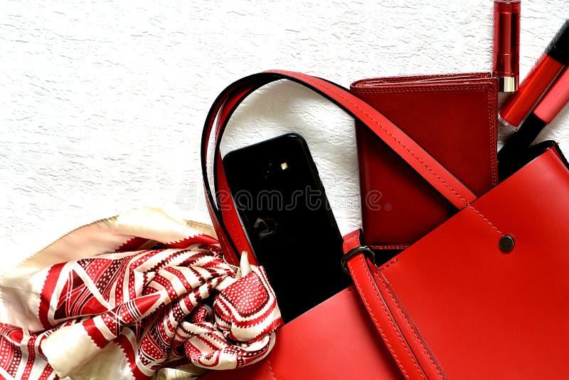 Borsa femminile rossa d'avanguardia che rovescia gli oggetti fotografie stock libere da diritti