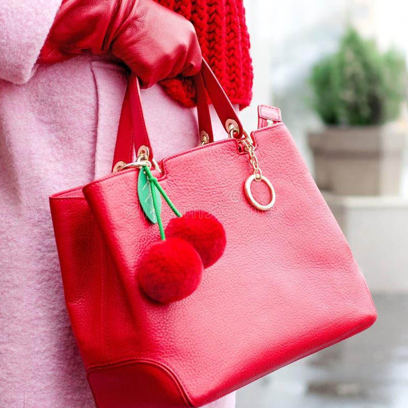 Borsa in mani femminili Borsa di cuoio luminosa accessori Cappotto rosa e borsa rossa ciliegia del ninnolo da pelliccia fotografia stock libera da diritti