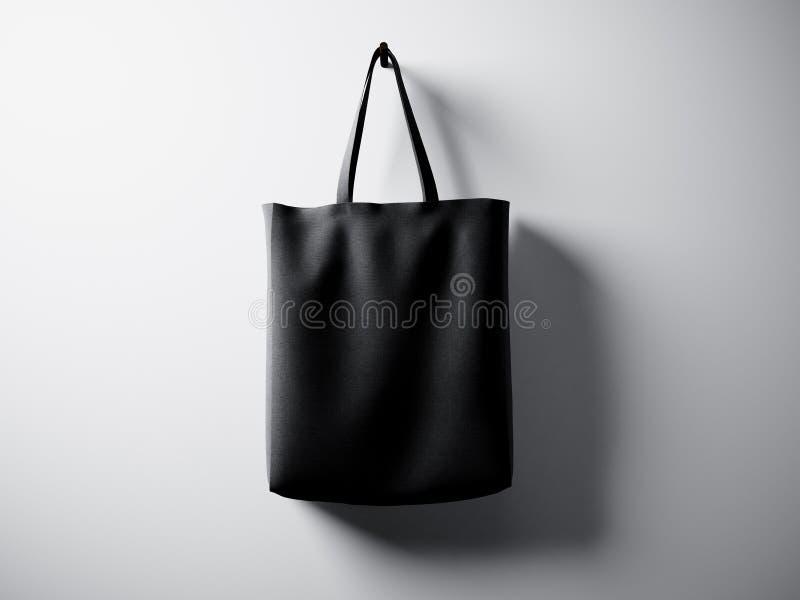 Borsa nera del tessuto di cotone della foto che appende nel centro Fondo bianco vuoto della parete Struttura altamente dettagliat fotografia stock
