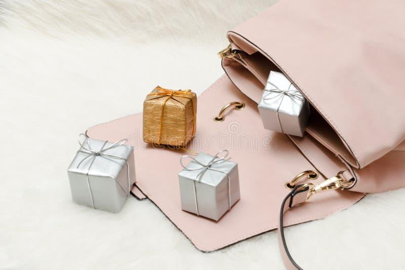 Borsa rosa con i piccoli contenitori di regalo Concetto di festa immagini stock