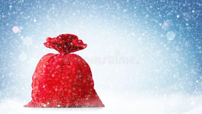 Borsa rossa di Santa Claus in pieno, su fondo blu con neve immagini stock