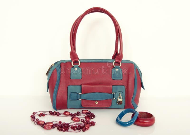 Borsa rossa e blu con la collana ed i braccialetti di corrispondenza fotografie stock