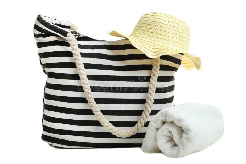 Borsa a strisce della spiaggia con l'asciugamano di bagno bianco ed il cappello delle donne della paglia fotografia stock