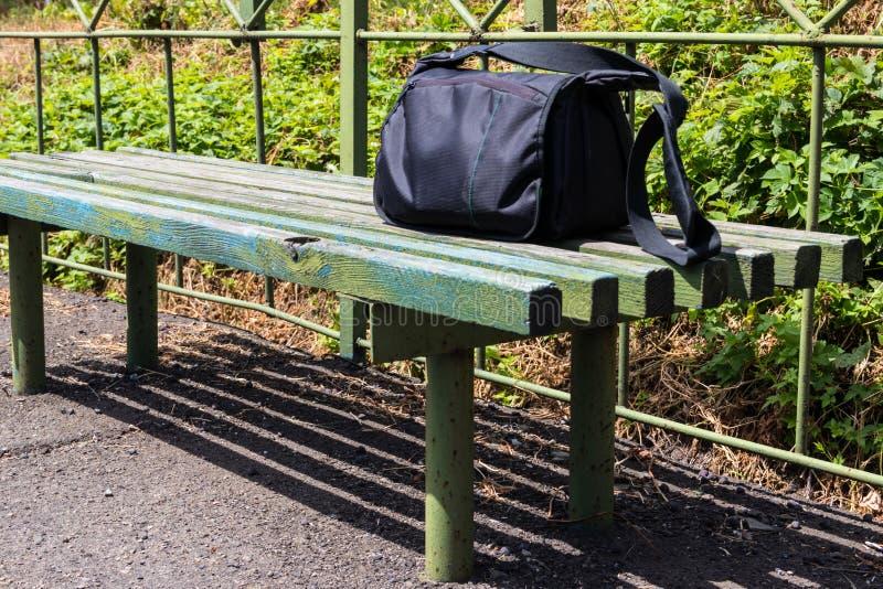 Borsa su un banco di legno sulla vecchia piattaforma della ferrovia alla campagna immagine stock libera da diritti