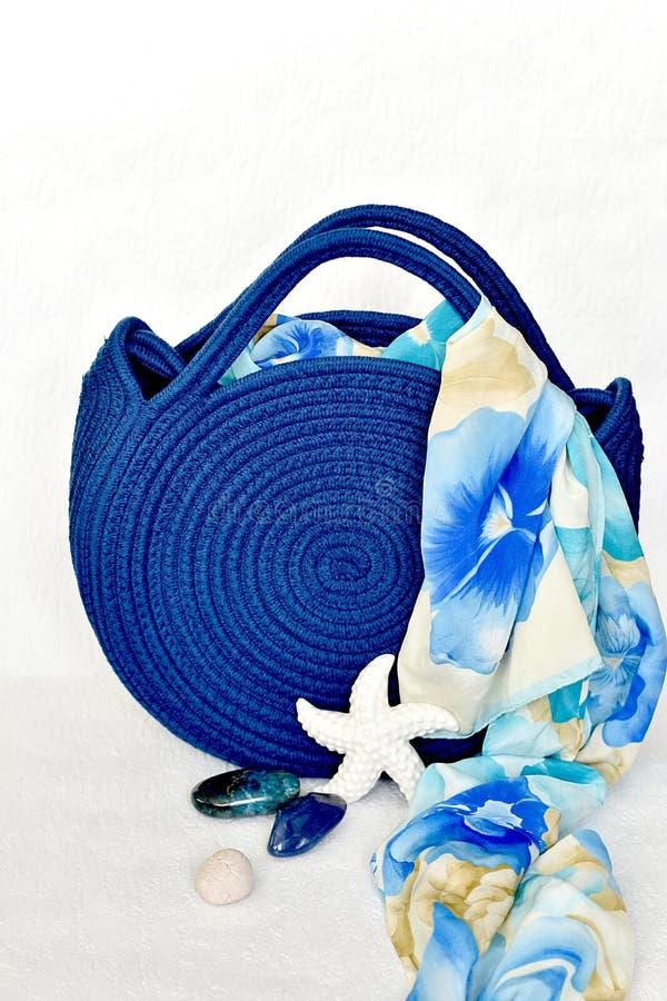 Borsa tricottata blu reale della spiaggia con il fondo floreale della sciarpa fotografia stock libera da diritti