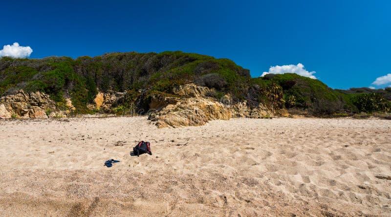 Borsa turistica con le scarpe sulla spiaggia bianca Erba e mazzi nel fondo Paesaggio tropicale esotico fotografia stock libera da diritti