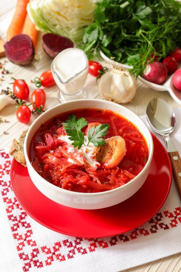 Borsch ucraino tradizionale della minestra su un tovagliolo bianco ricamato nello stile ucraino immagini stock