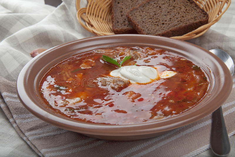 Borscht. Red fresh borscht with sour cream in the brown bowl on the table royalty free stock image
