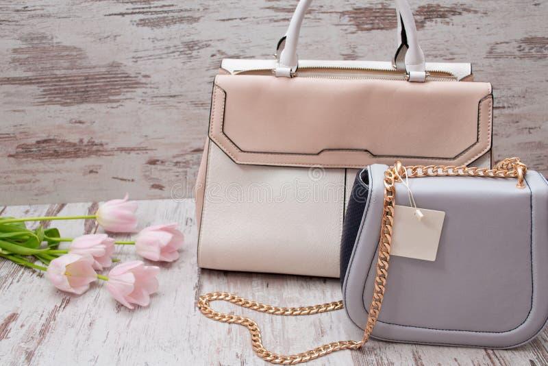 Borse beige e grige su un fondo di legno, tulipani rosa concetto alla moda immagine stock libera da diritti