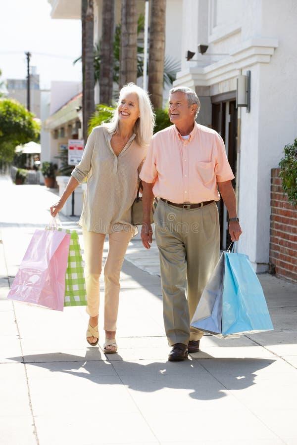 Borse di acquisto di trasporto delle coppie senior immagine stock