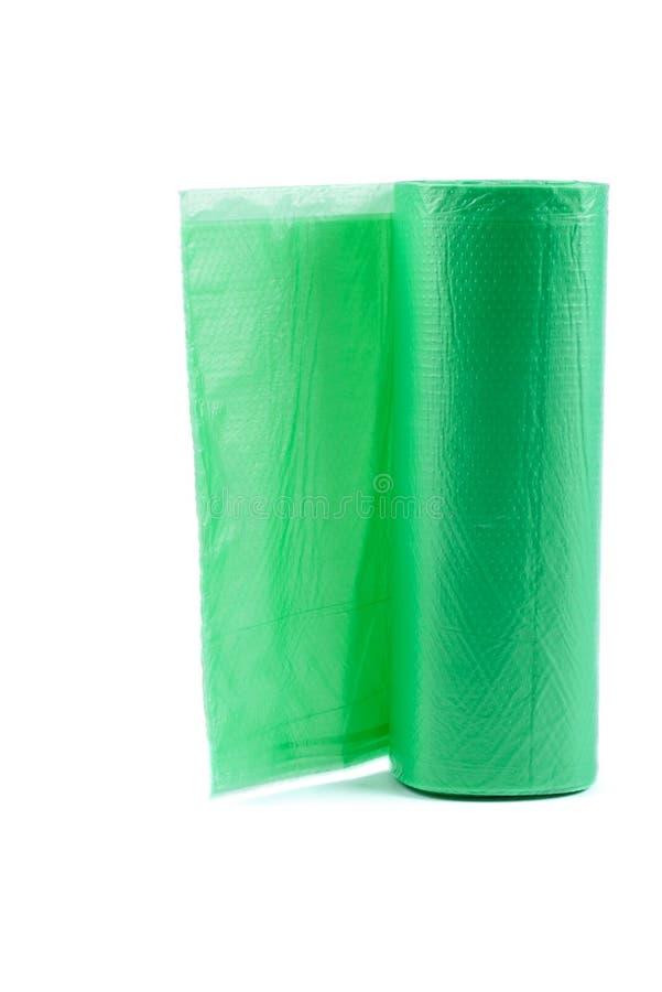 Borse di immondizia di plastica verdi del bagsRoll di plastica verde dell'immondizia del rotolo isolate sui precedenti bianchi fotografia stock