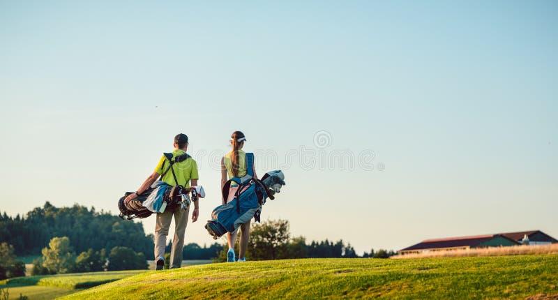 Borse di trasporto del supporto delle coppie felici verso il campo da golf in un giorno soleggiato immagini stock libere da diritti