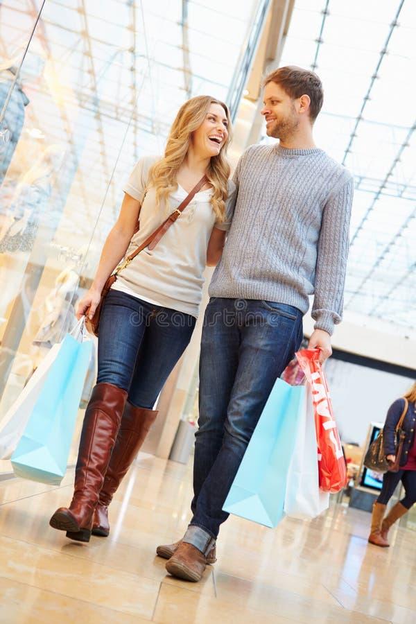 Borse di trasporto delle coppie felici nel centro commerciale immagini stock