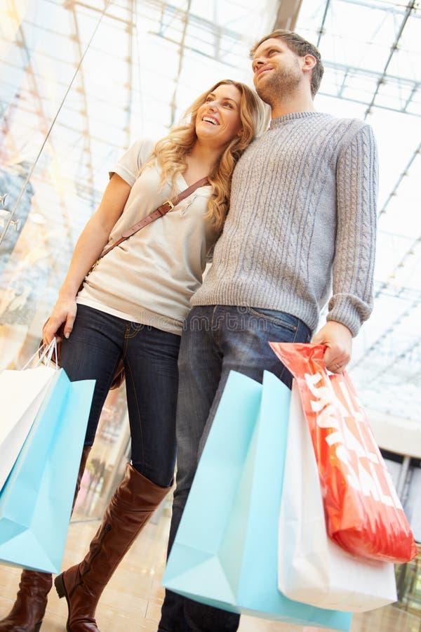 Borse di trasporto delle coppie felici nel centro commerciale fotografie stock