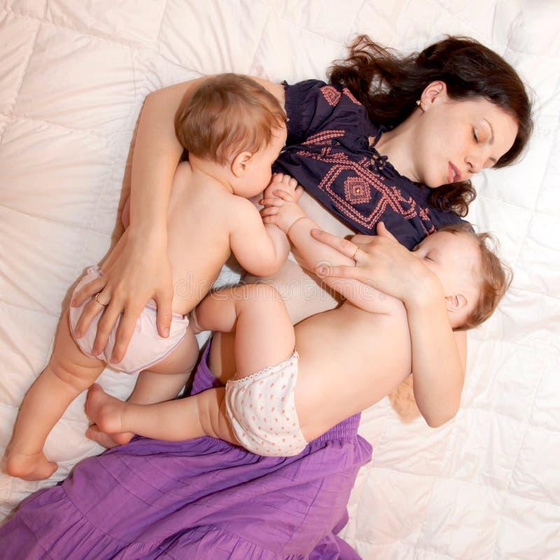 Borst die - twee kleine zusters voedt breng babymeisjes samen royalty-vrije stock foto's
