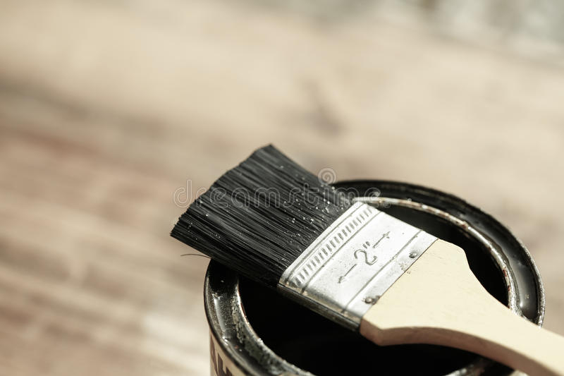 Borsta att vila på en tenn- can av skyddande målarfärg arkivbild