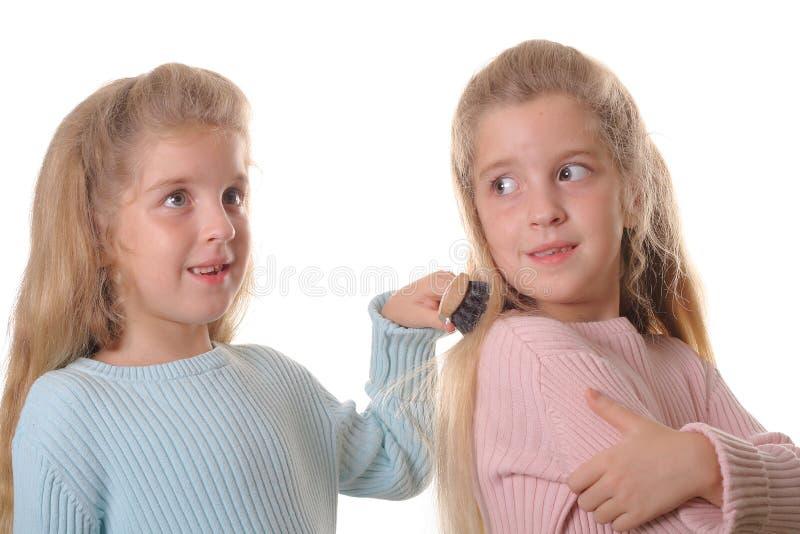 borsta barnhårsystrar kopplar samman fotografering för bildbyråer